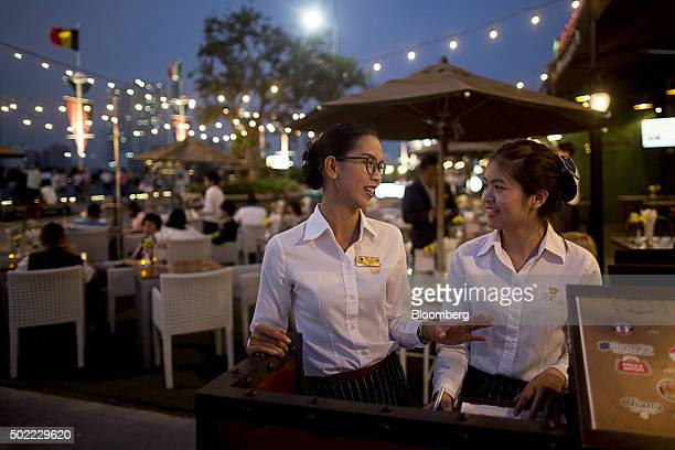 Employees stand talking at a restaurant at Asiatique The Riverfront openair mall in Bangkok Thailand on Friday Dec 18 2015 Thai economic indicators...