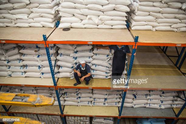 Employees take a break near bags of processed garlic stacked in bags inside a warehouse at a Nithi Foods Co factory in the San Pa Tong district of...