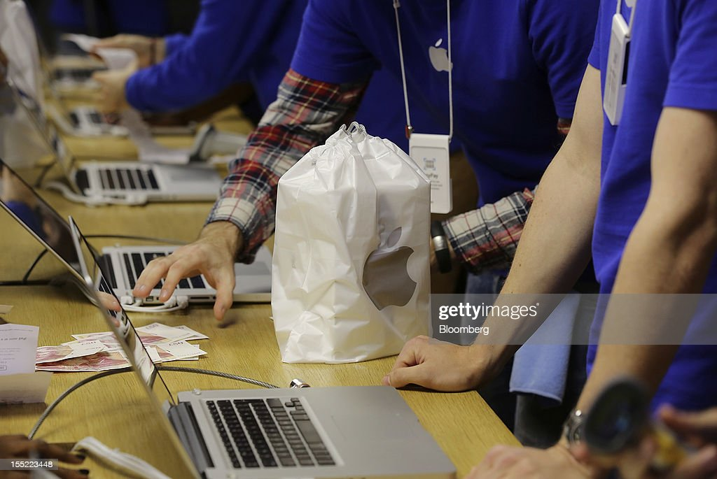 Employees take cash for a customer's purchase of an Apple Inc. iPad mini at the company's Covent Garden store in London, U.K., on Friday, Nov. 2, 2012. Apple Inc.'s iPad mini tablet goes on sale in the U.K. today. Photographer: Simon Dawson/Bloomberg via Getty Images