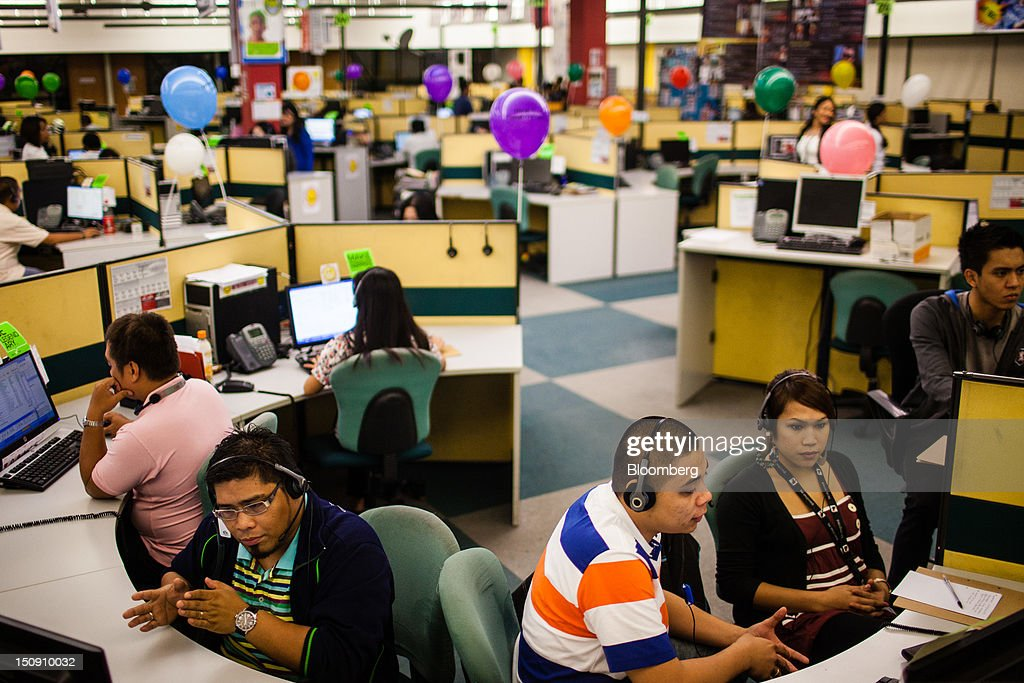 Employees take phone calls as they work in an SPi Global call center in Manila the Philippines on Tuesday Aug 28 2012 Manilabased SPi Global's 18000...
