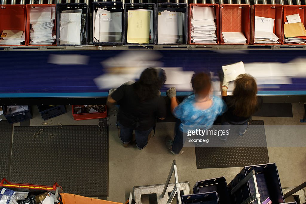 Employees take post from a conveyor belt at the PostNL NV mail sorting center in Nieuwegein, Netherlands, on Friday, Sept. 27, 2013. PostNL NV rose the most in two months on Sept. 19 after the Dutch postal operator raised its full-year forecast and announced higher prices for stamps. Photographer: Jasper Juinen/Bloomberg via Getty Images