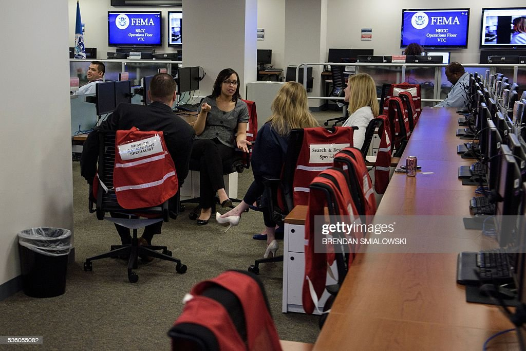 FEMA employees talk while US President Barack Obama meets with their superiors about hurricane season at the Federal Emergency Management Agency May 31, 2016 in Washington, DC. / AFP / Brendan Smialowski