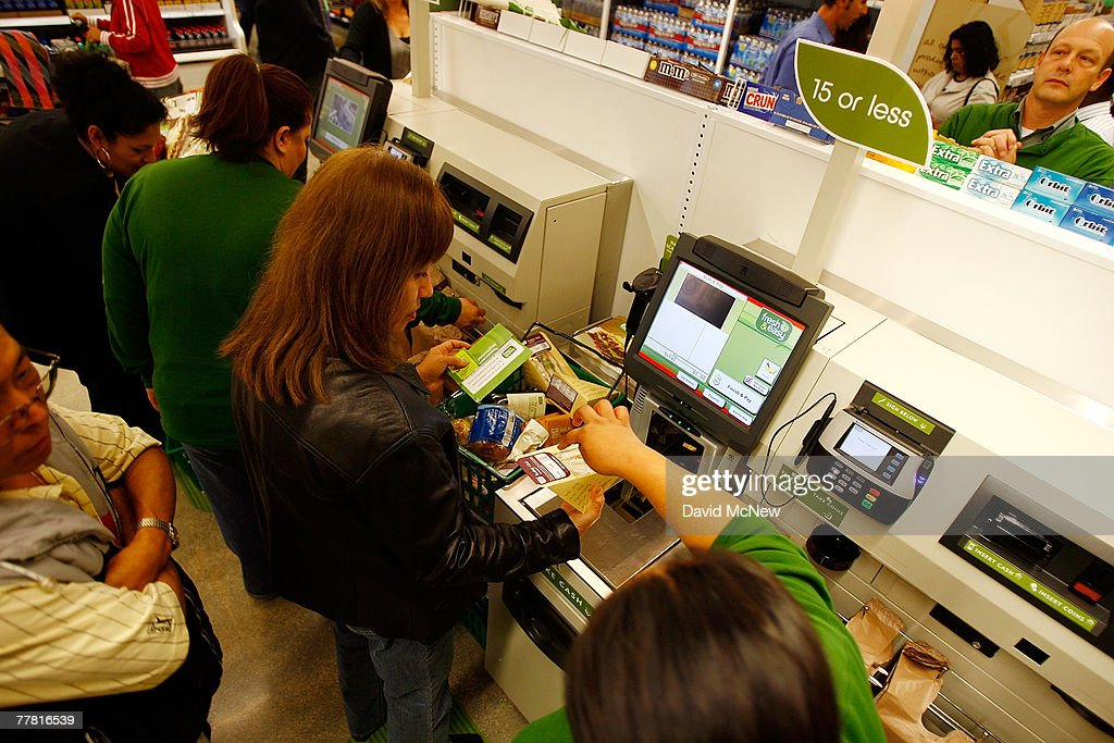 Employees teach shoppers to use selfservice checkout stations at a Fresh Easy grocery as Tesco PLC the UK's biggest retailer officially enters the US...