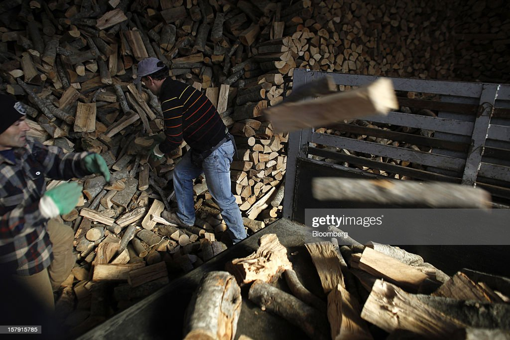 Employees throw logs into the back of a truck for delivery to customers at a wood store in Athens, Greece, on Friday, Dec. 7, 2012. Greece, the epicenter of Europe's debt crisis since revealing a bloated spending gap in late 2009, has faced regular demands to get a firmer grip on the budget or risk being forced out of the euro. Photographer: Kostas Tsironis/Bloomberg via Getty Images