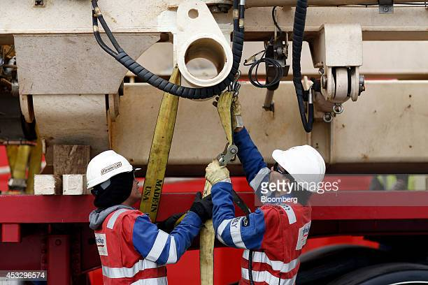 Employees tighten straps as they secure a section of shallow water roller box to a transport truck removed for repair from the offshore pipelay...