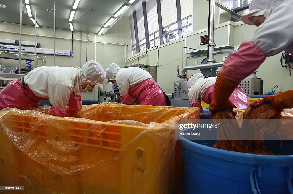 Employees transfer fermented kimchi from a yellow vat into a storage bin on the production line at the Gamchilbaegi Co. kimchi factory in Gwangju, South Korea, on Tuesday, Sept. 10, 2013. Gross domestic product rose 1.1 percent in the second quarter from the preceding three months, the most in more than two years, central bank data showed Sept. 5. Photographer: SeongJoon Cho/Bloomberg via Getty Images