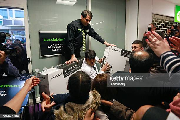 Employees try to control customers as they attempt to get the last remaining LED televisions during a Black Friday discount sale at an Asda...