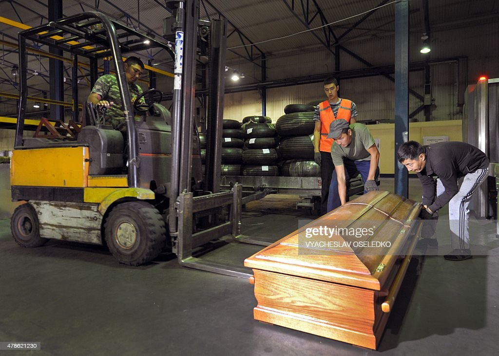Employees upload a coffin with the body of a Spanish climber into a plane at Manas airport 30 km from Bishkek on June 26 2015 before his repatriation...