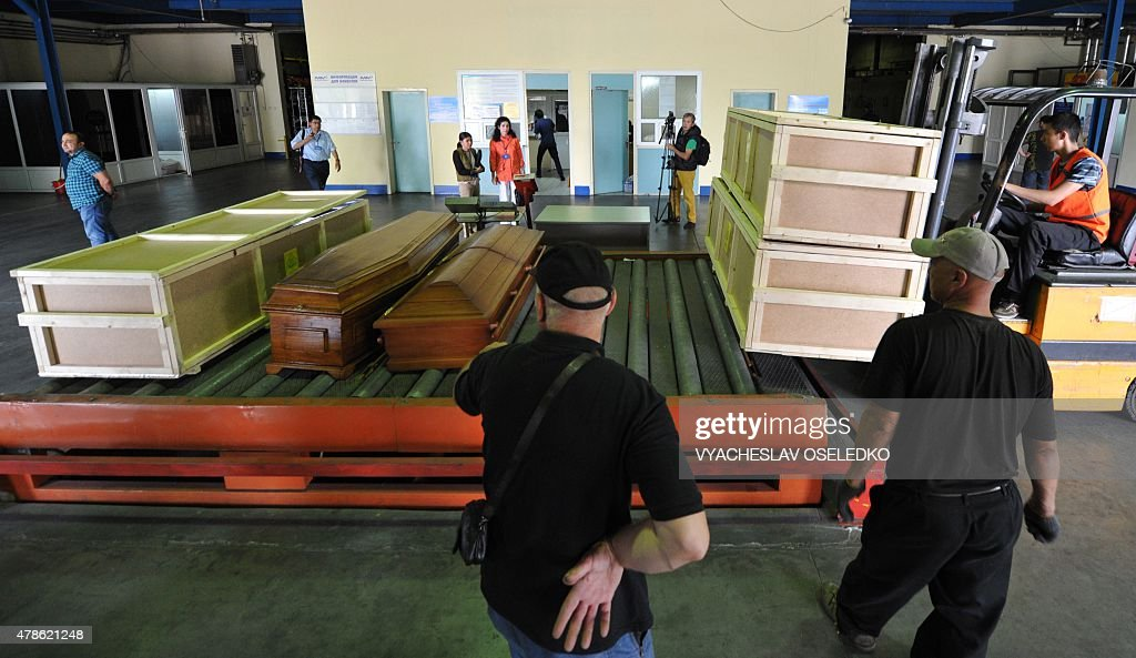 Employees upload coffins with the bodies of three Spanish climbers into a plane at Manas airport 30 km from Bishkek on June 26 2015 before their...