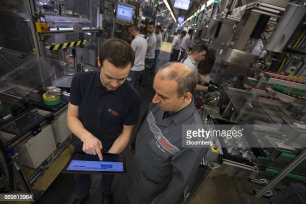 Employees use a tablet device to control the diesel automobile engine common rail pump production line at the Robert Bosch GmbH digital factory in...