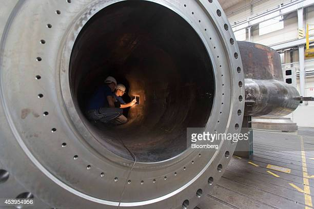 Employees use a torch inside a spiral case for a hydropower plant as they take measurements at the Voith GmbH factory in Heidenheim Germany on...