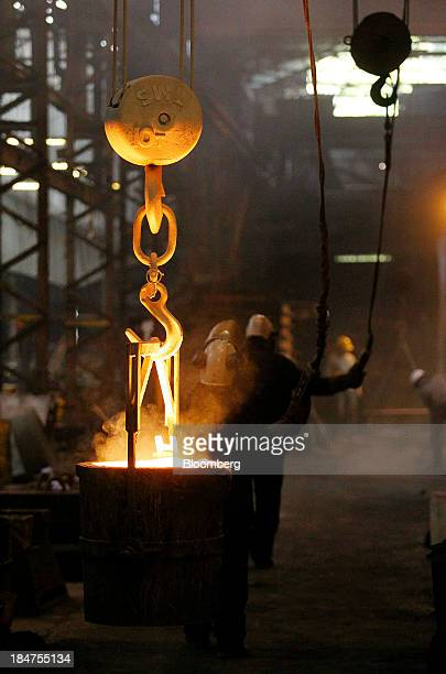 Employees use a winch to move a bucket of molten spheroidal graphite iron from the furnace towards a mould in the foundry at Specialised Castings Ltd...