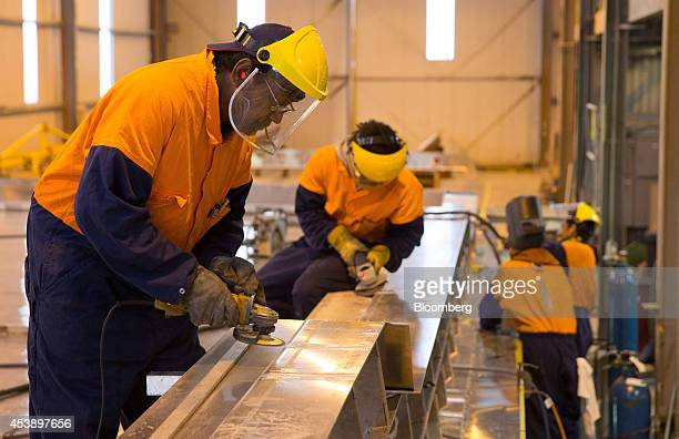 Employees use angle grinders during the construction of a 50meter superyacht in the McMullen Wing boatbuilding yard in Auckland New Zealand on...