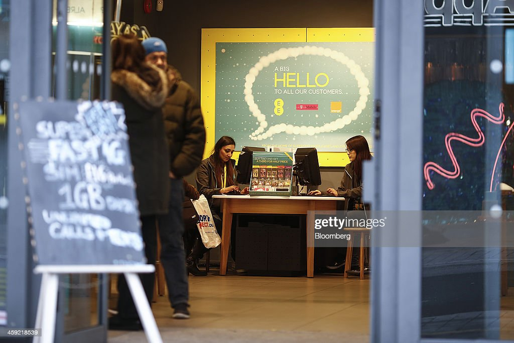 Employees use desk top computers as customers browse inside an EE mobile phone store in London, U.K., on Tuesday, Dec. 24, 2013. Vodafone Group Plc; EE, which is co-owned by Orange SA and Deutsche Telekom AG; Three, owned by Hutchison Whampoa Ltd.; and Virgin Media Inc. said they will cap bills run up on phones reported lost or stolen, stop mid-contract price increases, and support the U.K. government in its attempt to end roaming charges within the European Union. Photographer: Simon Dawson/Bloomberg via Getty Images