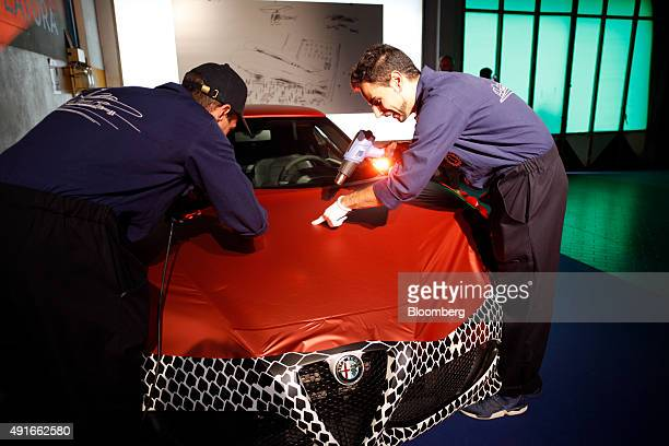 Employees use heat guns as they apply a vinyl wrapping to an Alfa Romeo 4C produced by Fiat Chrysler Automobiles NV during the launch of Garage...
