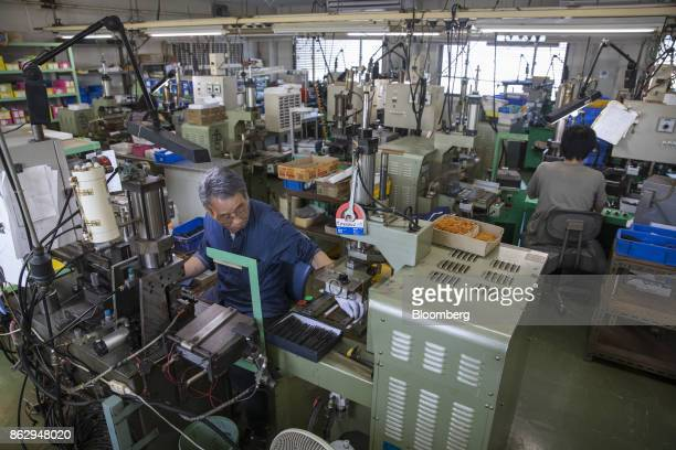 Employees use machinery to make eyeglass temples at a Nagai Co factory in Sabae Fukui Prefecture Japan on Tuesday Oct 10 2017 Fukui Prefecture has...