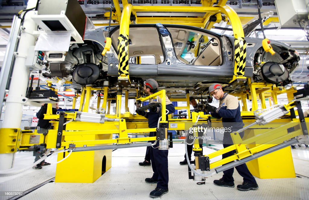 Employees use robotic arms as they work on the underside of a Maserati Quattroporte luxury automobile as it travels along the production line at Fiat SpA's Grugliasco factory in Turin, Italy, on Wednesday, Jan. 30, 2013. Fiat SpA Chief Executive Officer Sergio Marchionne said the Italian carmaker narrowed losses in Europe in the fourth quarter, helping it achieve full-year earnings that were in line with its forecasts. Photographer: Alessia Pierdomenico/Bloomberg via Getty Images