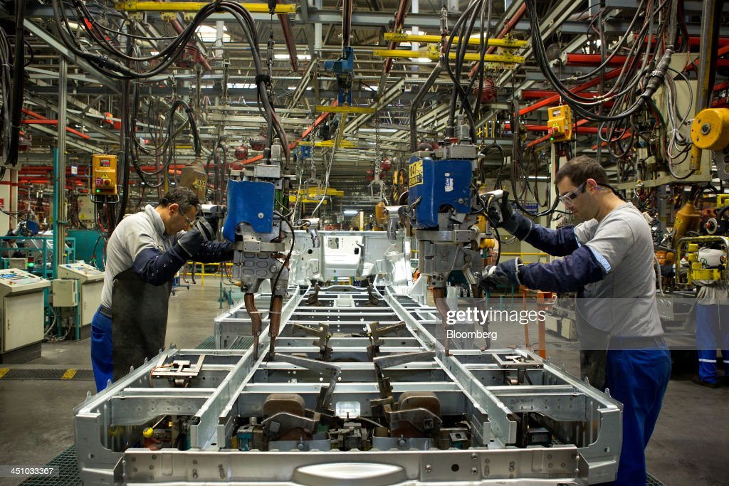Employees use suspended machines to weld the metal joints of a chassis on the Ford Transit van production line at the Ford Otosan plant, the joint venture between Ford Motor Co.'s Ford Otomotiv Sanayi AS and Koc Holding AS, in Golcuk, Turkey, on Wednesday, Nov. 20, 2013. Istanbul-based Automobile Distributors' Association, or ODD, forecasts Turkey's total automotive industry market to be between 830k and 870k this year. Photographer: Kerem Uzel/Bloomberg via Getty Images
