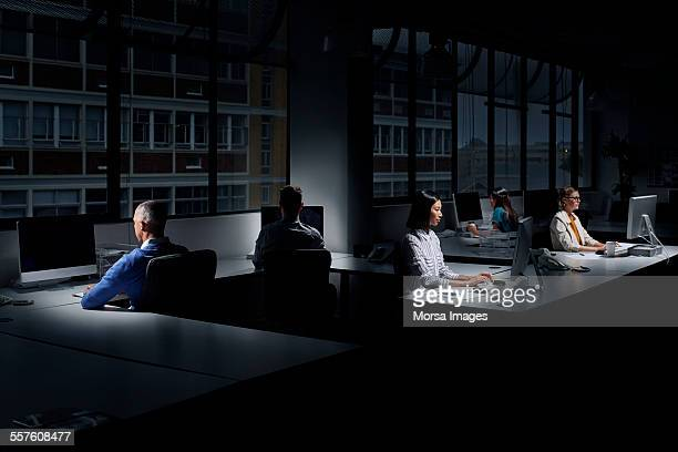 Employees using computers in dark office