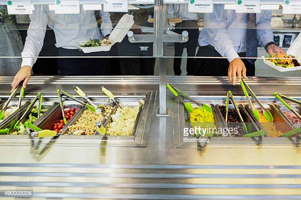 Employees visit the salad bar during lunch in the cafeteria of the Goldman Sachs Group Inc office in New York US on Thursday Sept 10 2015 Many of...