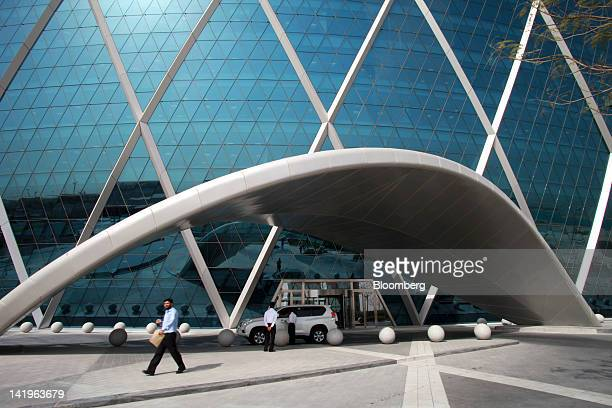 Employees wait by a vehicle at the entrance to the headquarters of Aldar Properties PJSC Abu Dhabi's biggest real estate company in Abu Dhabi United...