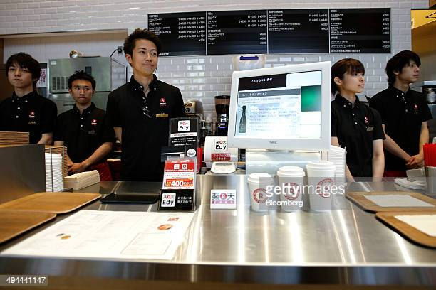 Employees wait for customers ahead of the opening of the Rakuten Cafe operated by Rakuten Inc in Tokyo Japan on Thursday May 29 2014 Japan's retail...