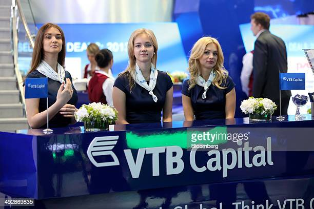 Employees wait to greet visitors to the VTB Capital OJSC pavilion on the opening day of the St Petersburg International Economic Forum in Saint...