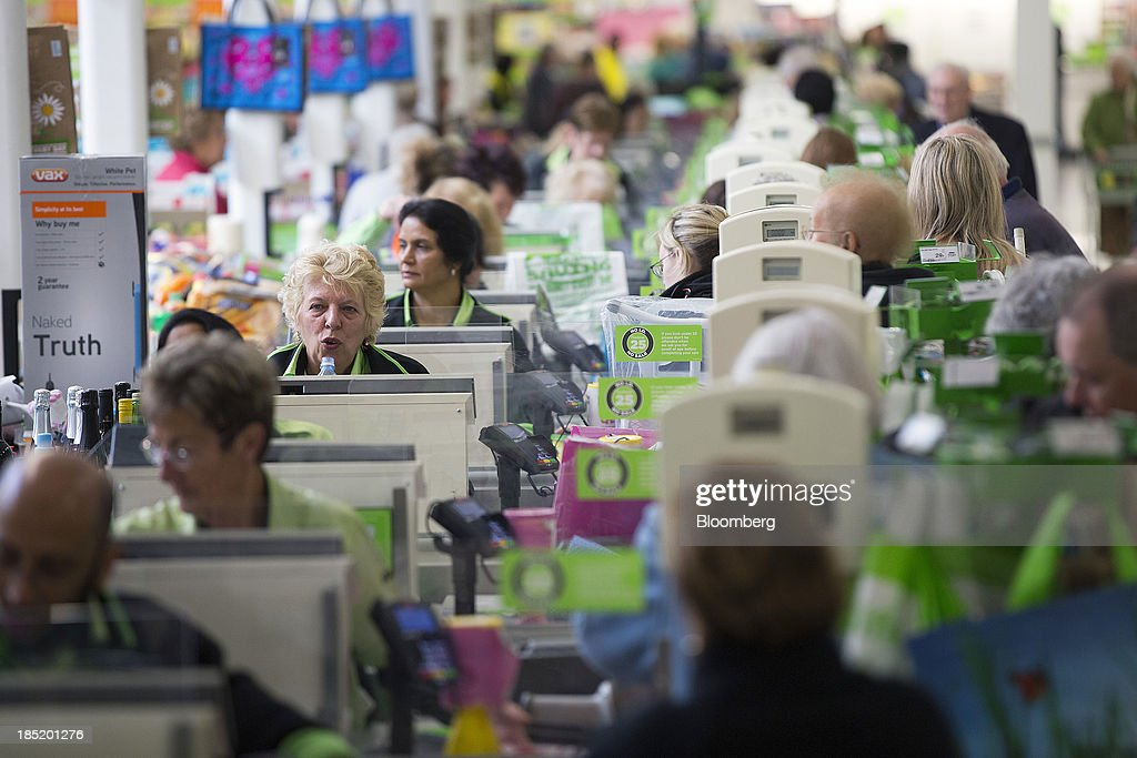 Employees wait to serve customers at check-out desks inside an Asda supermarket, the U.K. retail arm of Wal-Mart Stores Inc., in Watford, U.K., on Thursday, Oct. 17, 2013. U.K. retail sales rose more than economists forecast in September as an increase in furniture demand led a rebound from a slump the previous month. Photographer: Simon Dawson/Bloomberg via Getty Images