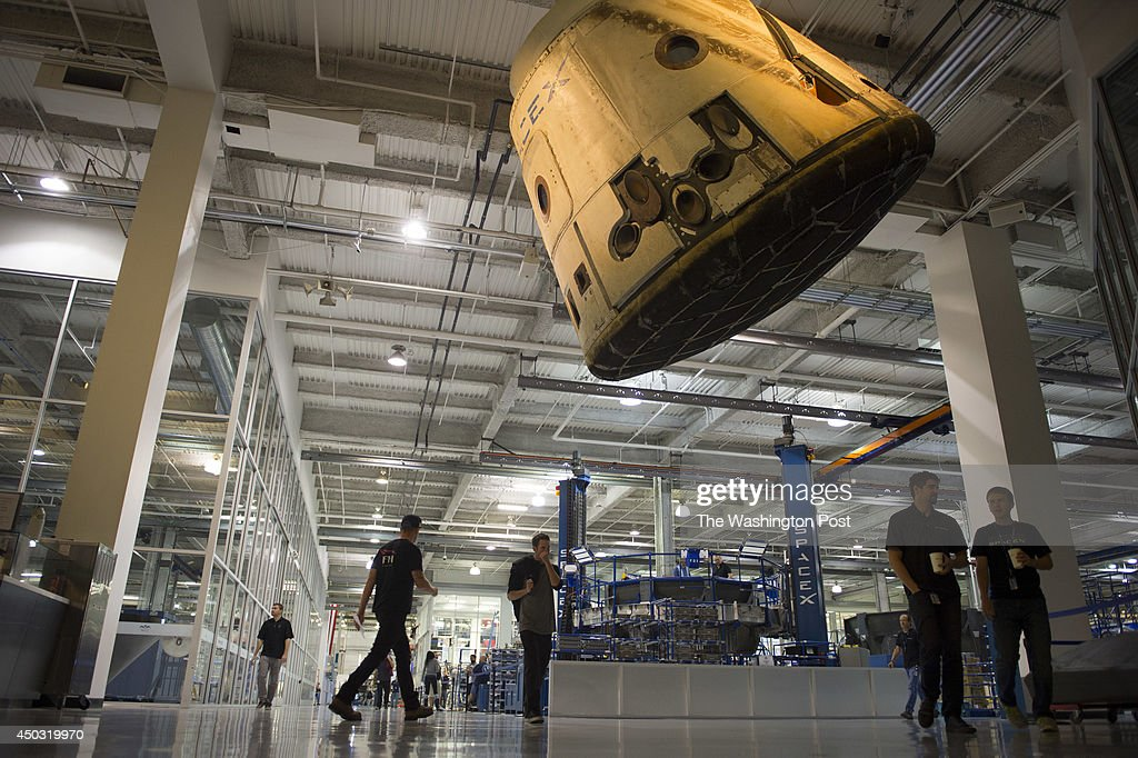 Employees walk beneath a Dragon spacecraft hanging from the ceiling on the factory floor at SpaceX on October 21 2013 in Los Angeles Ca