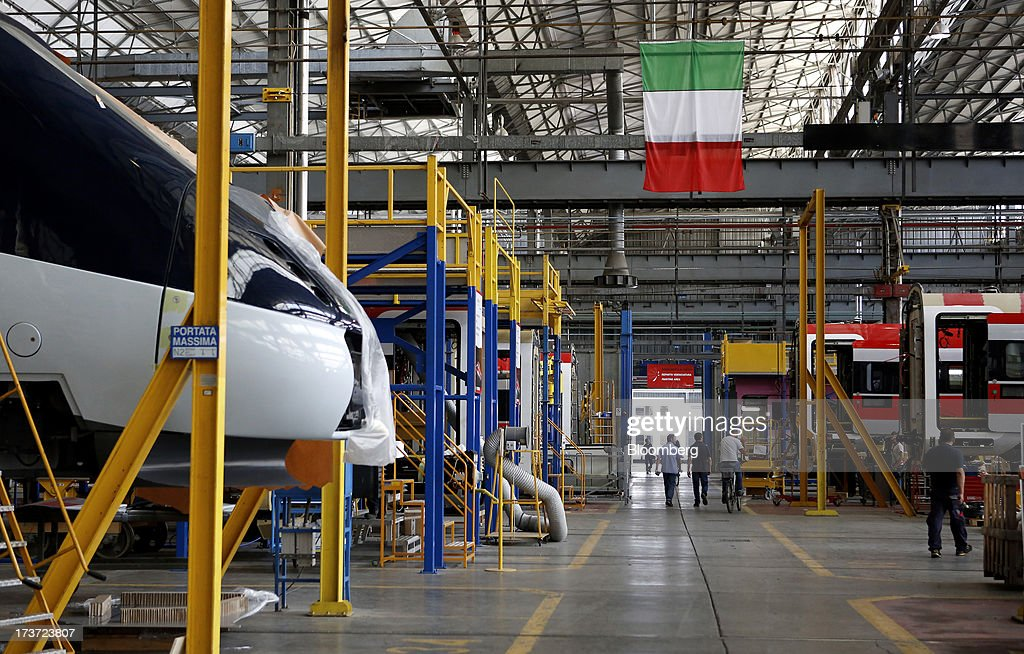 Employees walk beneath an Italian national flag as it hangs above the Frecciarossa 1000 high-speed train production line at AnsaldoBreda SpA's rail-car plant in Pistoia, Italy, on Tuesday, July 16, 2013. Italian business confidence rose last month after Prime Minister Enrico Letta's Cabinet passed plans to boost employment and postponed the payment of the value-added tax planned for July. Photographer: Alessia Pierdomenico/Bloomberg via Getty Images