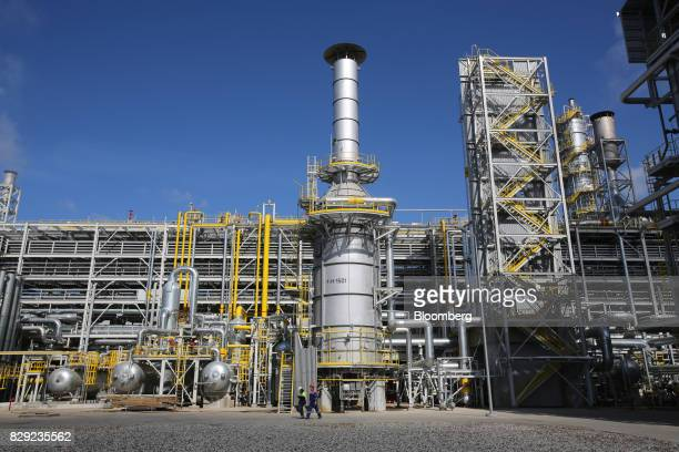 Employees walk by a new ammonia production unit currently under testing at the PhosAgroCherepovets fertilizer plant operated by PhosAgro PJSC in...