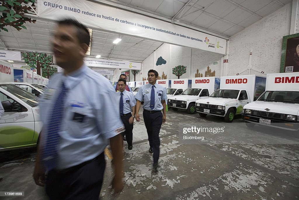 Employees walk by electric delivery trucks inside Grupo Bimbo SAB de CV's new sales center in Mexico City, Mexico, on Thursday, July 18, 2013. Grupo Bimbo inaugurated a new eco-friendly sales center today. Photographer: Susana Gonzalez/Bloomberg via Getty Images