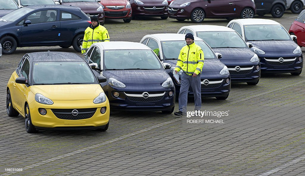 Employees walk by newly fabricated models of the Opel Adam car at the Opel plant in Eisenach, eastern Germany on January 10, 2013. The new Opel model will be produced as of January 10, 2013 at the Eisenach Opel plant and is intended to attract young automobile drivers in cities. Opel has already received 16 000 orders for the Adam. AFP PHOTO / ROBERT MICHAEL