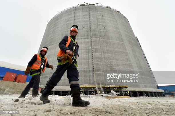 Employees walk close to a natural gas reservoir under construction at the port of Sabetta in the Kara Sea shore line on the Yamal Peninsula in the...