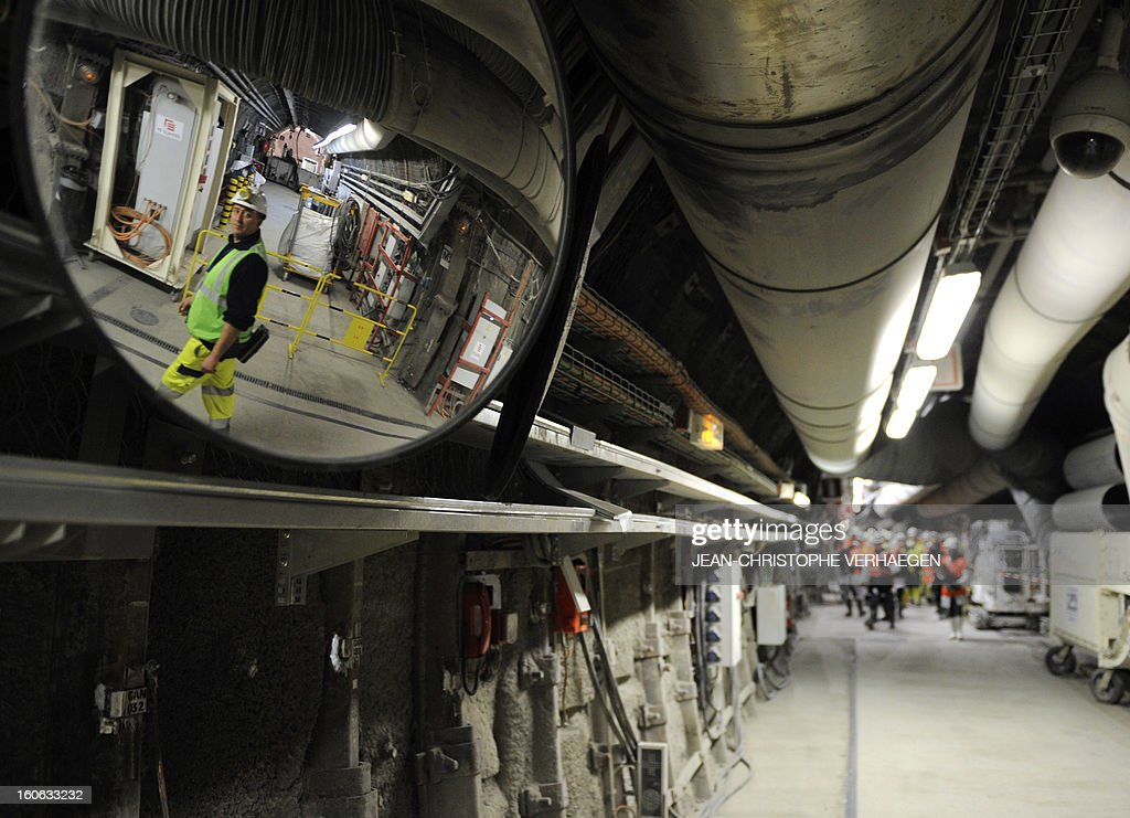 Employees walk in a corridor at the Underground Laboratory at Bure, eastern France, operated by the French National Radioactive Waste Management Agency (Andra), on February 4, 2013. AFP PHOTO / JEAN-CHRISTOPHE VERHAEGEN