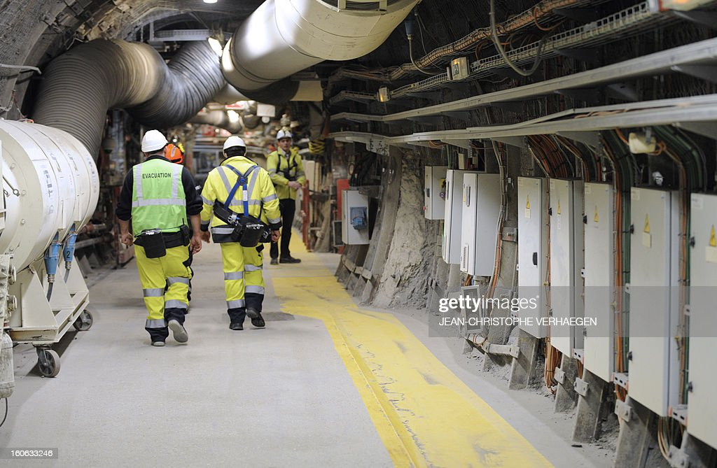 Employees walk in a corridor at the Underground Laboratory at Bure, eastern France, operated by the French National Radioactive Waste Management Agency (Andra), on February 4, 2013.