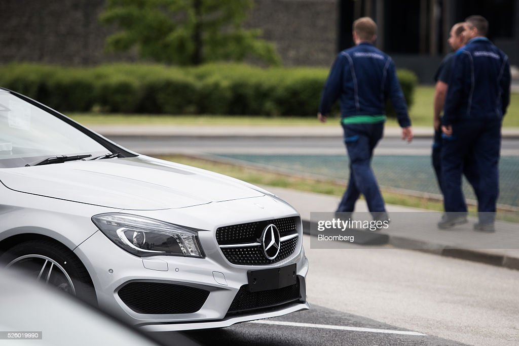 Employees walk past a CLA-class automobile parked outside the Mercedes-Benz AG automobile plant, operated by Daimler AG, in Kecskemet, Hungary, on Friday, April 29, 2016. Daimler's Mercedes factory will produce a new generation of compact vehicles, totalling Daimlers investment in Hungary to more than $1.8 billion. Photographer: Akos Stiller/Bloomberg via Getty Images