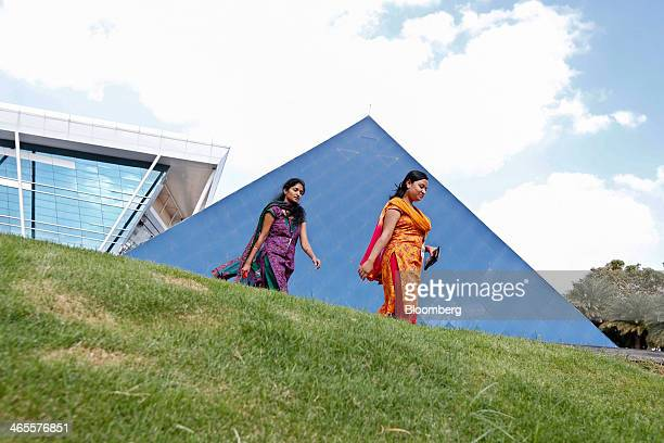 Employees walk past a pyramid shaped building at the Infosys Ltd campus in Electronics City in Bangalore India on Monday Jan 27 2013 Infosys India's...