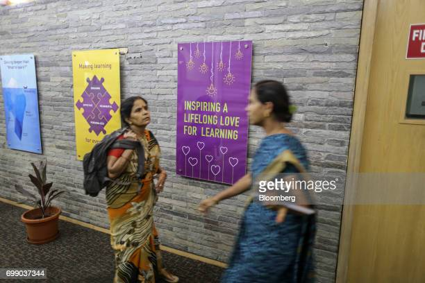 Employees walk past advertisements for BYJU'S learning app in the Think and Learn Pvt office in Bengaluru India on Wednesday April 5 2017 Online...