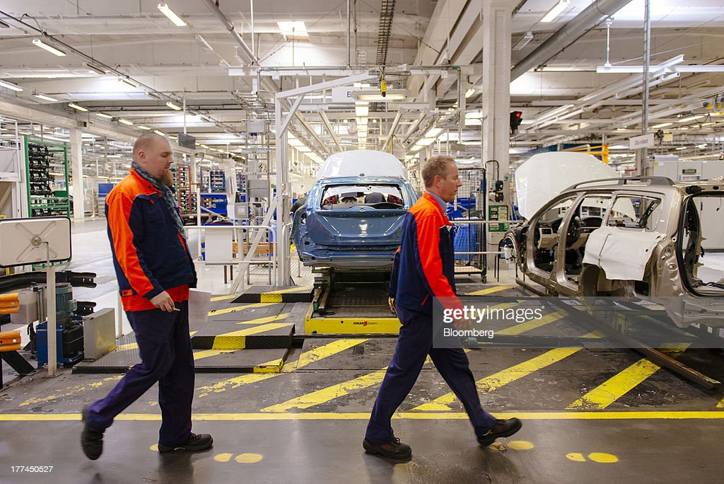 Employees walk past automobile chassis on the production line at the Volvo Cars plant in Torslanda, Sweden, on Thursday, Aug. 22, 2013. Volvo Cars Chief Executive Officer Hakan Samuelsson will settle a German investigation into corruption allegations linked to his tenure as MAN SE's CEO by paying 500,000 euros ($668,000) to charity. Photographer: Kristian Helgesen/Bloomberg via Getty Images