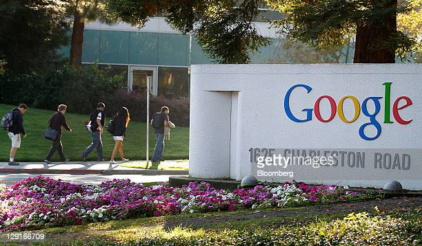 Employees walk past Google Inc signage while arriving for work at company headquarters in Mountain View California US on Thursday Oct 13 2011 Google...