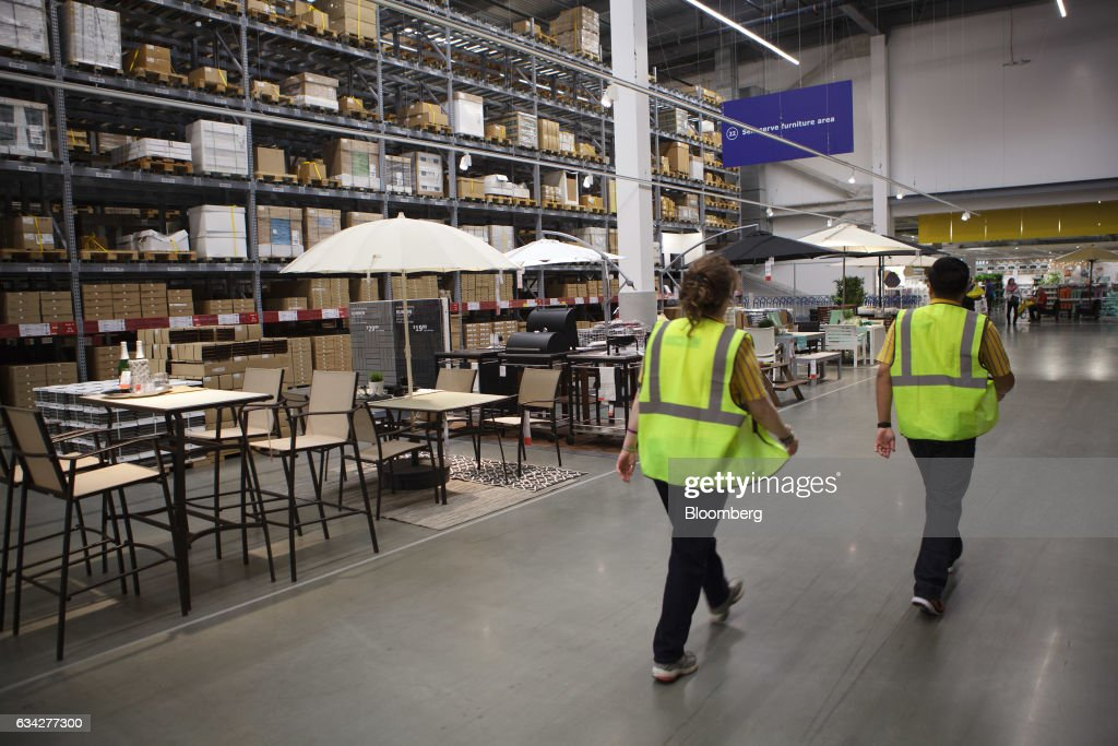 Employees Walk Past Outside Furniture Displayed For Sale At The New IKEA  Sweden AB Store During
