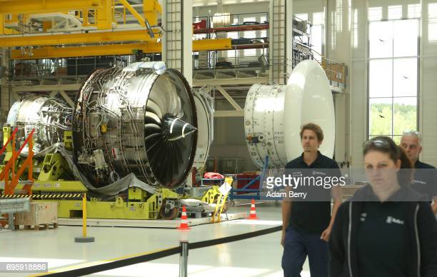 Employees walk through the production floor of the assembly line for the RollsRoyce Trent XWB airplane engine to be used in the Airbus A350 XWB...
