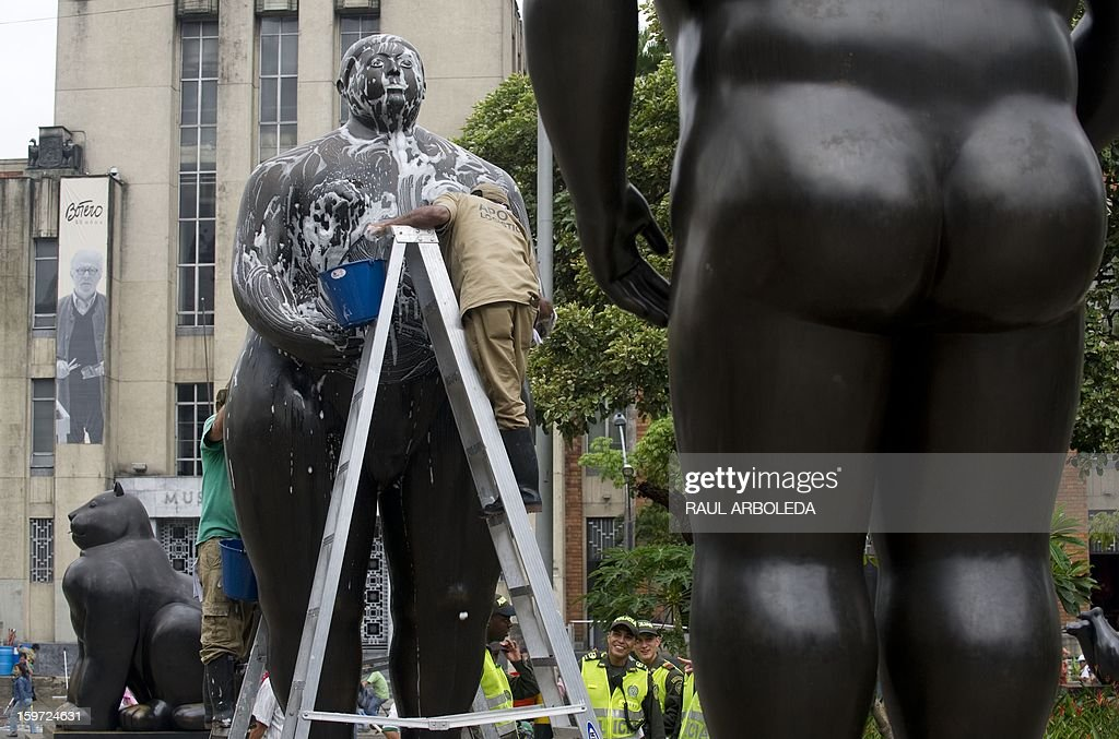Employees wash the sculpture 'Eva' by Colombian artist Fernando Botero, in Medellin, Antioquia Department, on January 19, 2013. Each year the Antioquia museum leads a cleanup day of the 23 sculptures displayed at Botero square. AFP PHOTO/Raul ARBOLEDA