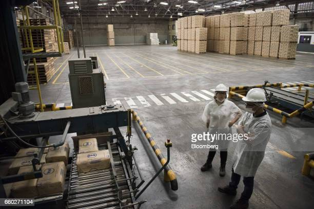 Employees watch as sacks of Empresas Polar SA PAN brand cornmeal are packaged for transport at the company's processing and distribution facility in...