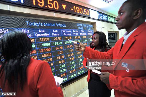 Employees watch stock prices displayed on an electronic screen inside the Nairobi Securities Exchange Ltd in Nairobi Kenya on Tuesday Dec 8 2015 The...