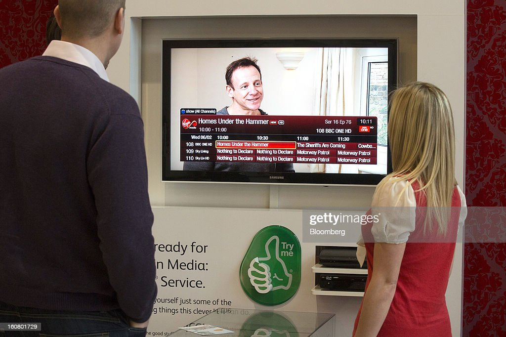 Employees watch the television via the Virgin Media Tivo set-top box inside Virgin Media's reception area at the company's headquarters on the Bartley Wood Business Park in Hook, U.K., on Wednesday, Feb. 6, 2013. Billionaire John Malone's Liberty Global Inc. agreed to acquire Virgin Media, Britain's second-largest pay-TV provider, in a $16 billion cash-and-stock transaction announced in the U.S. yesterday. Photographer: Simon Dawson/Bloomberg via Getty Images
