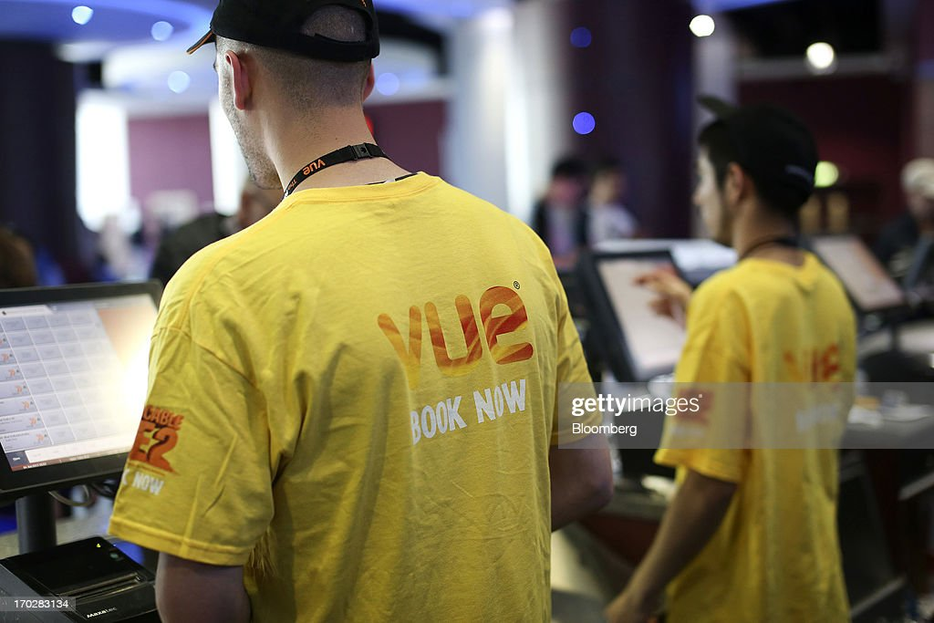Employees wear branded t-shirts as they serve customers at a sales counter inside a Vue Cinema, operated by Vue Entertainment Ltd., at the Westfield Stratford City retail complex in London, U.K., on Tuesday, June 4, 2013. Vue Entertainment, the U.K. cinema chain bought by private equity firm Doughty Hanson & Co., are continuing to expand in Europe, recently acquiring Poland's second-largest cinema chain Multikino. Photographer: Chris Ratcliffe/Bloomberg via Getty Images