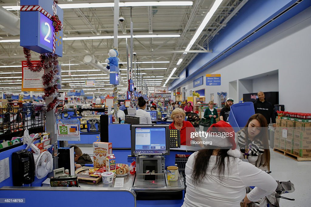 Employees wear Santa hats as customers check out at a Wal-Mart Stores Inc. location ahead of Black Friday in Los Angeles, California, U.S., on Tuesday, Nov. 26, 2013. Wal-Mart Stores Inc. said Doug McMillon, head of its international business, will replace Mike Duke as chief executive officer when he retires as the world's largest retailer struggles to ignite growth at home and abroad. Photographer: Patrick T. Fallon/Bloomberg via Getty Images