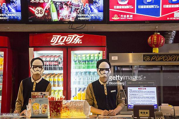 Employees wearing Storm Trooper masks wait to serve customers before the first public screening of Walt Disney Co's 'Star Wars The Force Awakens' at...